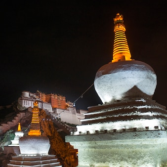 Vista di angolo basso di uno stupa con il palazzo di potala nei precedenti, lhasa, tibet, cina