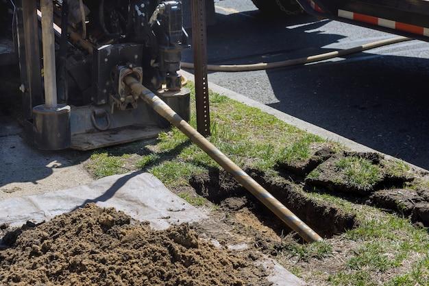 Vista ad angolo basso della posa senza scavo di comunicazioni, fibre ottiche e tubi dell'acqua con processo di lavoro della macchina con tecnologia di perforazione direzionale orizzontale
