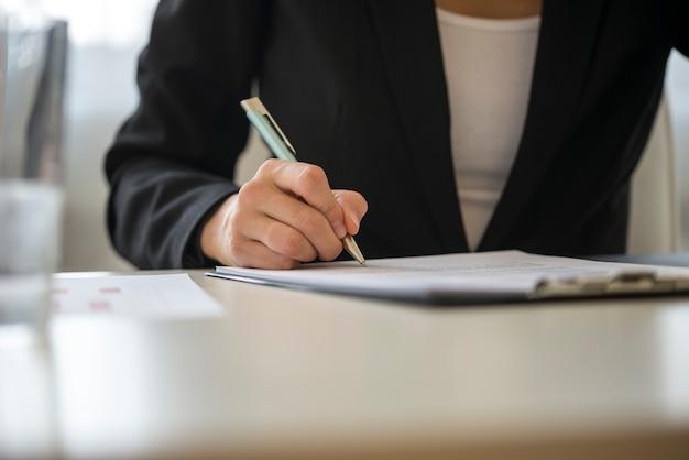Vista di angolo basso di un contratto di firma della donna