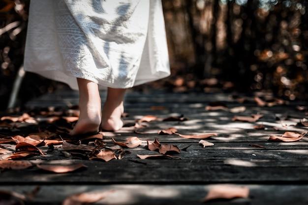 Punto di vista di angolo basso della donna in vestito bianco che cammina a piedi nudi nella foresta scura