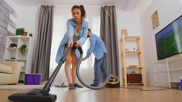 Angolo basso della giovane donna che lava il pavimento con la scopa.