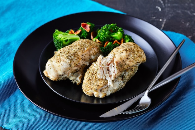 Filetto di pollo magro al forno con condimento ranch servito su un piatto nero con broccoli e pancetta