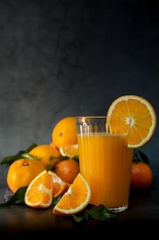 Immagine chiara chiave bassa di un bicchiere di succo d'arancia fresco accanto a una serie di arance pronte per essere spremute