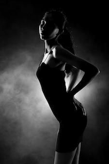 Ritratto scuro di donna magra e sana in sfondo nero con nebbia e luce dalla parte posteriore, curva di posa sexy con pantaloni corti e ombra, concetto di bianco e nero