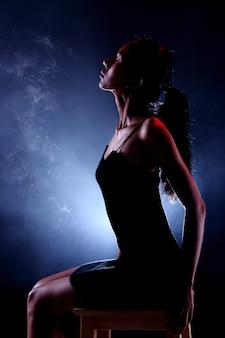 Ritratto scuro di donna magra e sana su sfondo nero con nebbia e luce dalla schiena, curva di posa sexy con pantaloni corti e ombra
