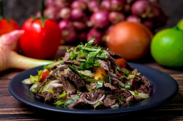 Fotografia di cibo in condizioni di scarsa illuminazione di insalata di carne piccante