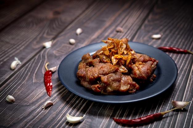 Fotografie con scarsa illuminazione di maiale fritto con aglio pronto per essere servito