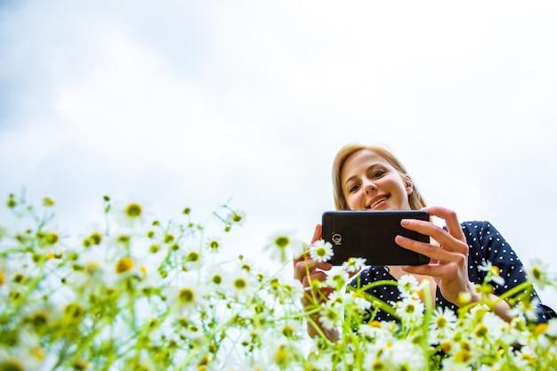 Basso punto di vista come donna bionda sta facendo una foto di fiori di camomilla
