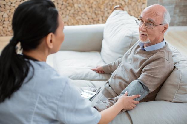 Bassa pressione. medico che indossa l'uniforme durante l'utilizzo del tonometro e il trattamento di bell'uomo anziano attraente