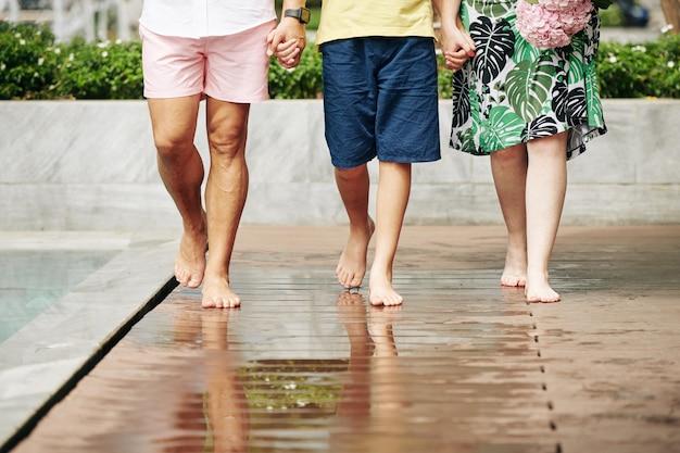 Sezione bassa di padre, madre e figlio che si tengono per mano quando si cammina sul pavimento bagnato accanto alla piscina all'aperto dell'hotel