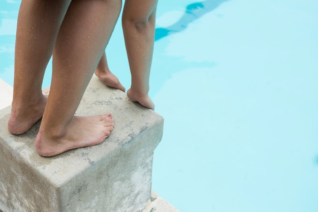 Sezione bassa del nuotatore femminile che prepara a tuffarsi in piscina