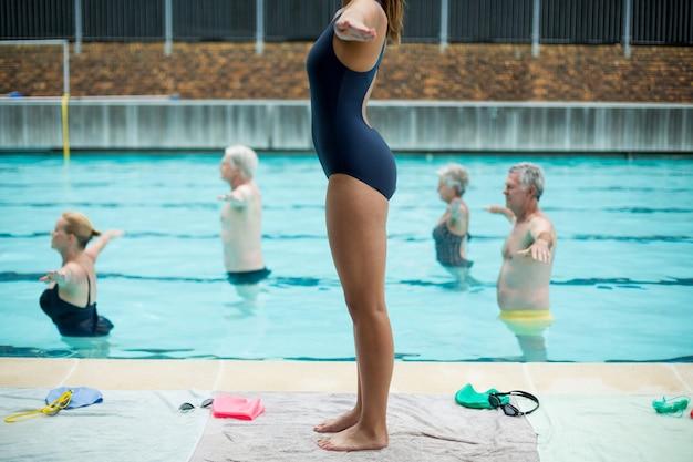 Sezione bassa dell'addestratore femminile che prepara nuotatori senior