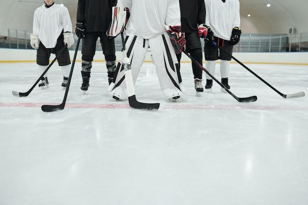 Sezione bassa di diversi giocatori di hockey e del loro allenatore in divisa sportiva, guanti e pattini in piedi sulla pista di pattinaggio allo stadio e con in mano dei bastoni