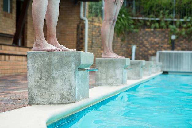 Sezione bassa di due donne anziane che si preparano a tuffarsi in piscina