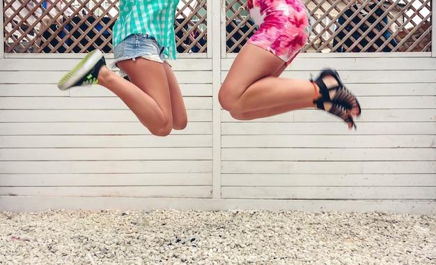 Sezione bassa di due donne irriconoscibili che saltano sullo sfondo bianco del recinto del giardino