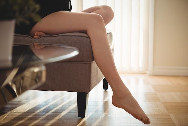 Sezione bassa della donna seduta sul divano