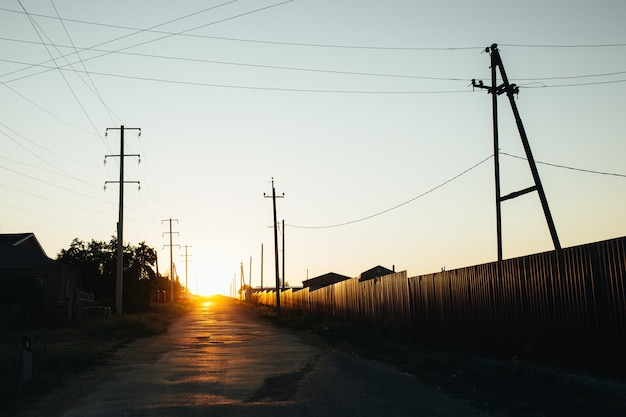 Il sole basso del tramonto splende su una strada rurale. ci sono edifici privati a sinistra della strada.