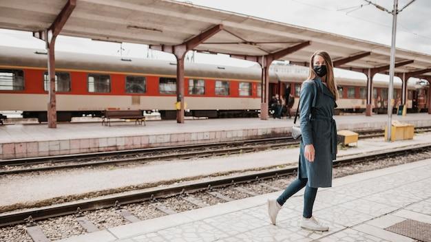 Vista bassa della donna che cammina a fianco della piattaforma ferroviaria