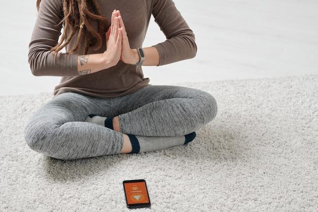 Parte inferiore della ragazza attiva seduta sul pavimento con le gambe incrociate e le mani unite dal petto