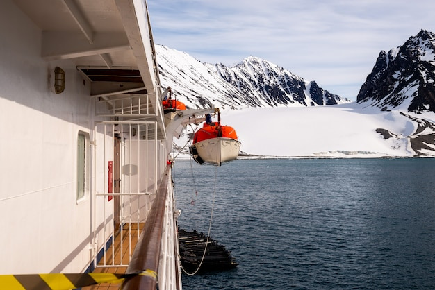 Abbassamento della scialuppa di salvataggio arancione per innaffiare nelle acque artiche, svalbard abbandonare il trapano per nave. addestramento della scialuppa di salvataggio. trapano uomo a mare.
