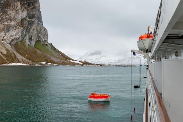 Abbassando la scialuppa di salvataggio arancione per innaffiare nelle acque artiche, le svalbard. abbandonare il trapano per nave. addestramento della scialuppa di salvataggio. trapano uomo a mare.