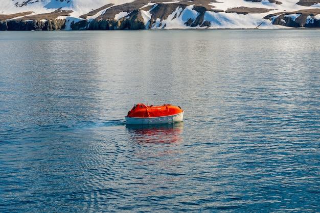 Abbassamento della scialuppa di salvataggio arancione per innaffiare nelle acque artiche