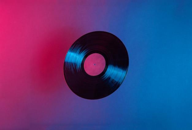 Disco in vinile lp illuminato con luce al neon colorata blu e rossa