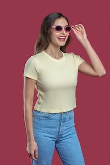 Giorno fortunato. giovane donna dai capelli lunghi allegra in jeans e maglietta che raddrizza i vetri di ottimo umore