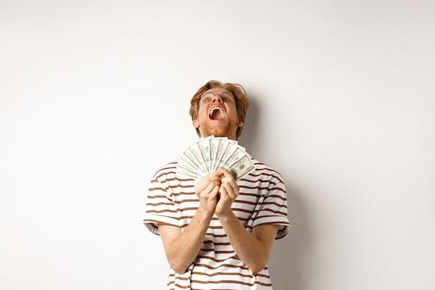 Uomo rosso fortunato che vince, che mostra il premio in denaro e urla di felicità ringraziando dio, alzando lo sguardo grato, in piedi su sfondo bianco.