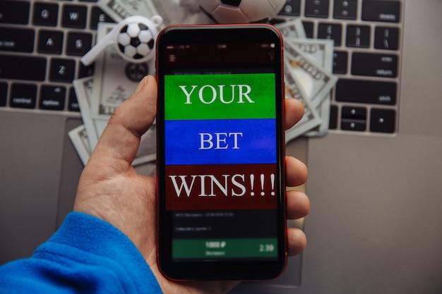 Fortunato vincitore alle scommesse sul calcio con il telefono in mano. fatture del dollaro e pallone da calcio su una tastiera. scommesse in linea concetto.