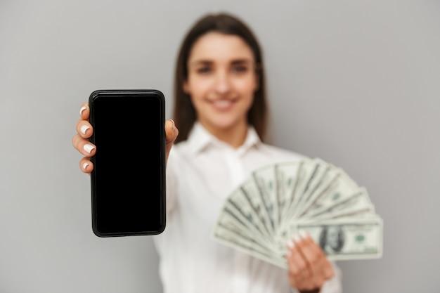 La donna fortunata 20s in bianco e nero indossa sorridente e dimostrando lo schermo nero copyspace del telefono cellulare con un sacco di soldi in mano, isolato sopra il muro grigio