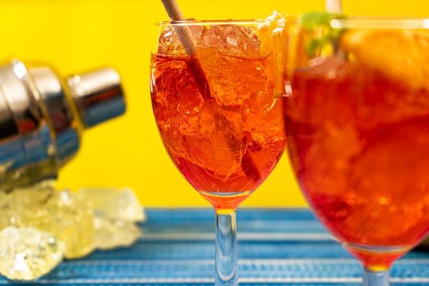 Lue tavolo con bicchieri di aperol spritz cocktail con foglie di menta e arancia e shaker per bottiglie