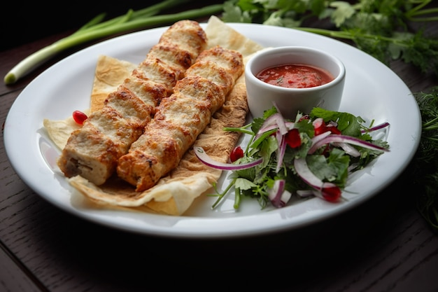 Kebab di lula con erbe e salsa, pollo
