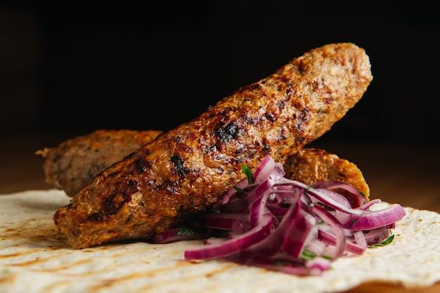 Lula kebab con pane pita e cipolla