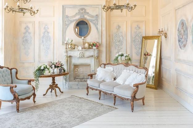 Luluxury ricco salotto interno in colore pastello beige con mobili antichi costosi in stile barocco. pareti decorate con stucchi e affreschi