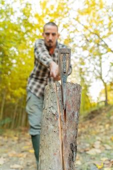 Uomo del boscaiolo tagliato con l'ascia polvere e movimenti taglialegna seghe albero con motosega su segheria