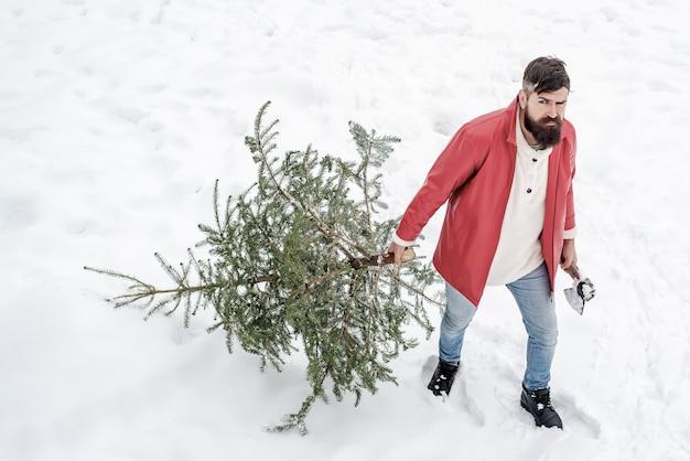 Boscaiolo santa in piedi con ascia e albero di natale su sfondo di neve.