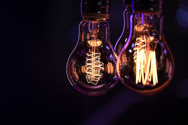 Lampade luminose pendono nell'oscurità dal muro. concetto di arredamento e atmosfera.