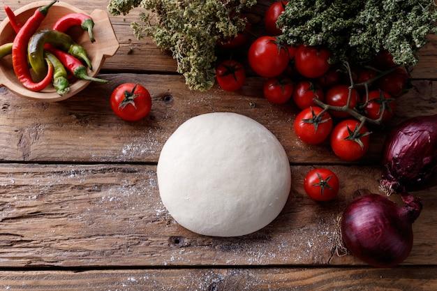 Pezzo di pasta su un tavolo di legno circondato da pomodori, pepe e cipolle
