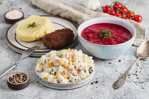 Pranzo in ciotola e piatti con forchetta e cucchiaio, panno da cucina e pomodori su fondo marmo chiaro light