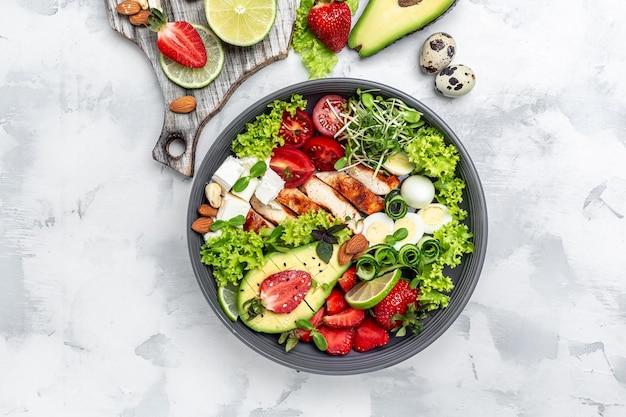 Ciotola per il pranzo con pollo, avocado, feta, uova di quaglia, fragole, noci e lattuga. detox e concetto di ciotola di supercibi sani. vista dall'alto.