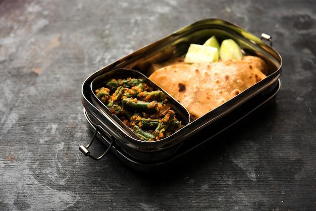 Lunch box o tiffin per bambini indiani, include fagioli vegetali sabzi con roti o chapati, messa a fuoco selettiva