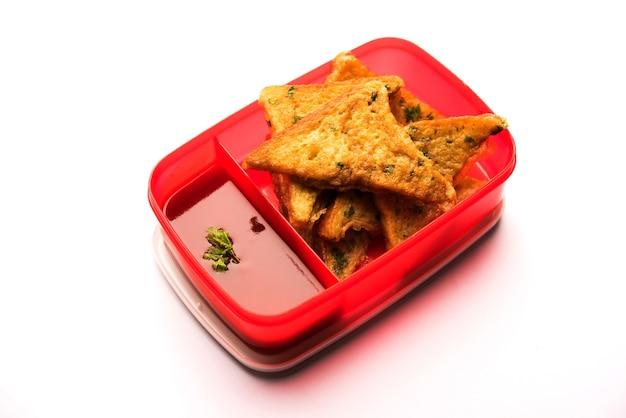 Lunch box o tiffin per bambini indiani, include pane frittata pakora con ketchup o germogli, messa a fuoco selettiva
