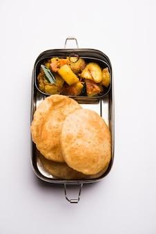 Lunch box o tiffin per bambini indiani, include hot poori, puri con patate, aloo sabzi, messa a fuoco selettiva