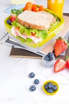 Scatola di pranzo e pane tostato con prosciutto e frutti di bosco su uno sfondo bianco
