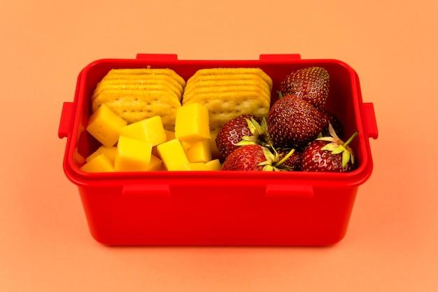 Lunch box con biscotti, pezzi di formaggio e fragole su sfondo arancione