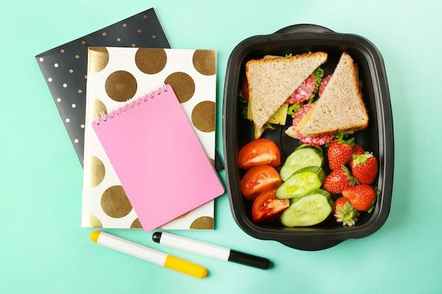 Scatola di pranzo con cibo e articoli di cancelleria su sfondo turchese