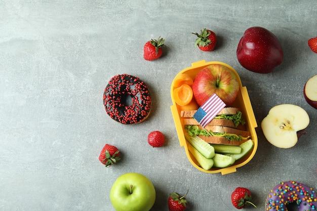 Lunch box con cibo gustoso e bandiera americana su sfondo grigio strutturato