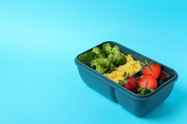 Lunch box con cibo gustoso su sfondo blu Foto Premium