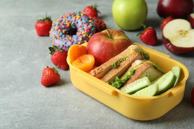 Lunch box con cibo gustoso su sfondo grigio strutturato